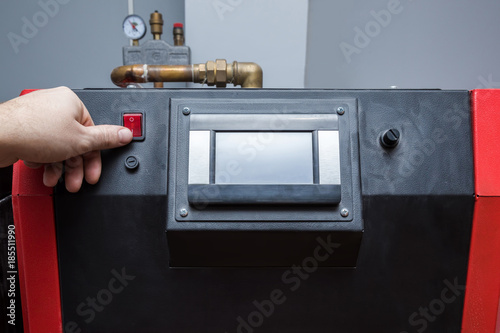 Photo  Man's finger turn on heater system's red start button in the boiler room