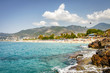 Landscape of resort sea beach in lagoon bay on summer sunny day. Rocky beach and mountains on horizon in tropical sea town. Beautiful paradise nature of Turkey perfect for relax.