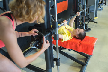 fitness-trainer assisting young female in lifting barbell in the gym