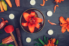 Tibetan Singing Bowl With Floating In Water Lily Inside. Special Sticks, Burning Candles, Lily Flowers And Petals On The Black Wooden Background. Meditation And Relax. Exotic Massage. Selective Focus.