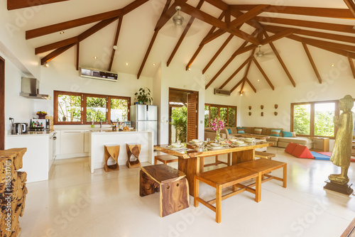 Luxury villa living room with kitchen interior. White walls and ...