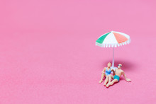 Miniature People Wearing Swimsuit Relaxing On Pink Background