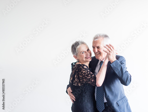 Fotografia  Mid length view of elegantly dressed older man and woman dancing against neutral