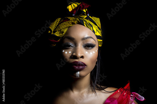 Fotografie, Obraz  Black female showing African pride by wearing Nigerian traditional clothing and tribal makeup or face painting
