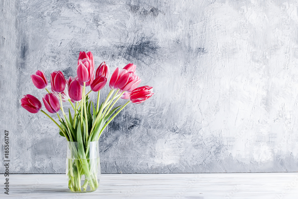 Bouquet of pink tulips in a glass vase on grey background.