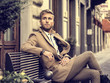 canvas print picture - Handsome man wearing elegant coat sitting on bench at street and posing relaxed.