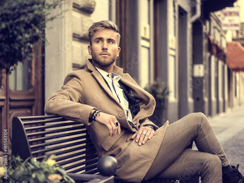 Stampa su Tela Handsome man wearing elegant coat sitting on bench at street and posing relaxed