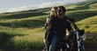 Attractive couple on vintage motorcycle watching the sunset