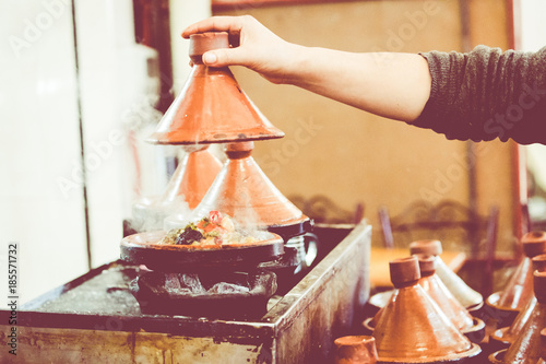 Cooking traditional Moroccan dish, meat and vegetable in ceramic tajine in Marrakech in Morocco.