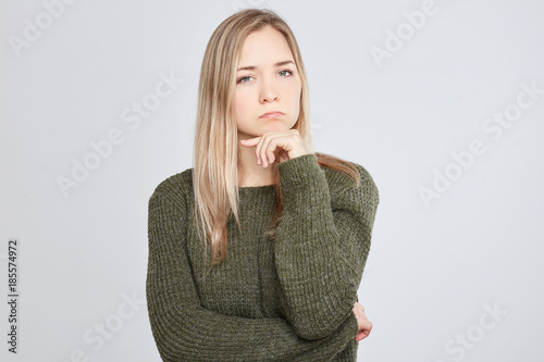 Cuadros en Lienzo Studio shot of beautiful European female woman with grumpy expression being offended after quarrel with parents or boyfriend