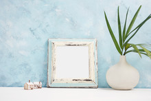 Square Blue Photo Frame Mock Up With Green Tropical Plants In Vaseand Small Wooden Houses On Shelf. Scandinavian Style.  Text Space