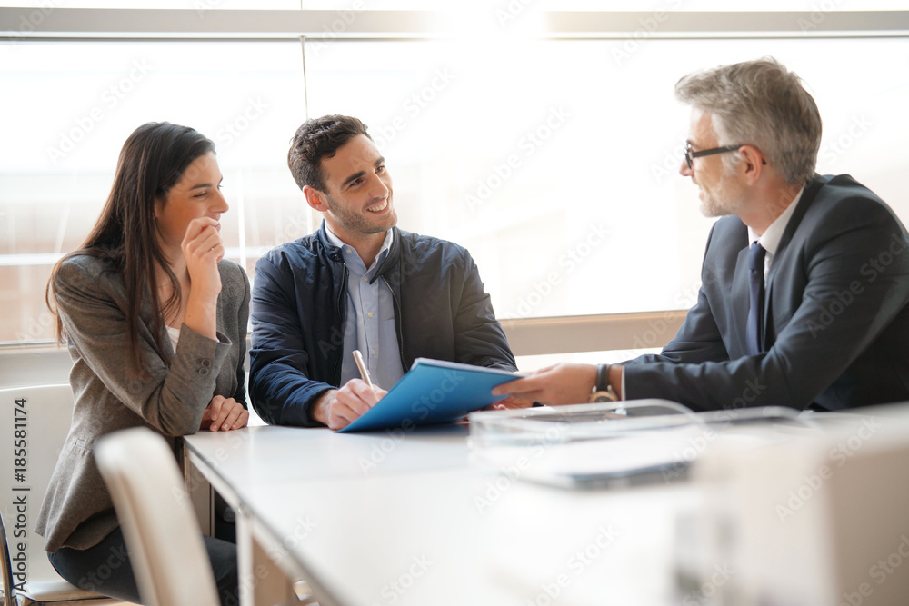 Fototapeta Young couple meeting financial advisor for home investment