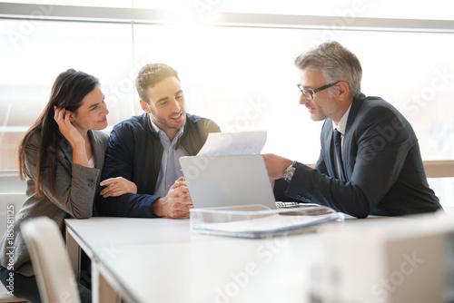 Fototapeta Young couple meeting financial advisor for home investment obraz