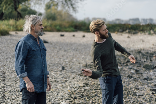 Father and son spending time together, son skipping pebbles