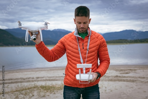 Man holding drone and remote control at riverside
