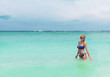 Young pretty blond woman in blue bikini on white tropic beach