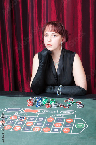 Plakat  ludomania, lass wearing  black gloves and black dress parlays in a casino