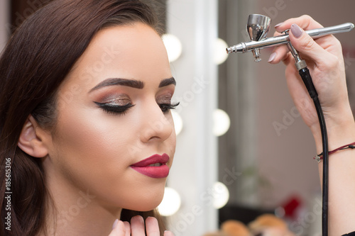 Makeup artist using airbrusher. Canvas Print