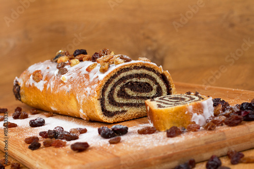 Fotografia  poppy seed lying on a wooden slate sprinkled with raisins and powdered sugar on