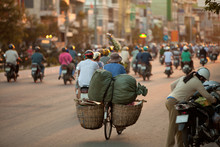 Evening Rush Hour In Asian City, A Lot Of People On Motorcycles Are Driving On The Road Against The Sunset/motorcycle Is The Main Mode Of Transport In Many Countries Of Asia/bicycle With Two Baskets