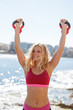 Young blonde woman pushing up into air kettlebells