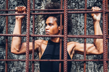 All Power To The People, Afro American Athlete Girl With Strong Arms After Workout Behind Iron Bars