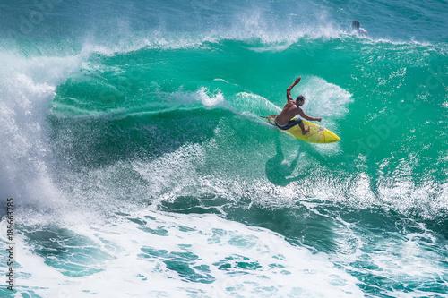 Foto  Surfer riding big green wave at Padang Padang beach, Bali, Indonesia
