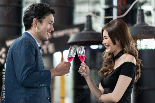 Fotografie, Obraz  Portrait of smiling young man and woman talking while holding red sparkling wine glass