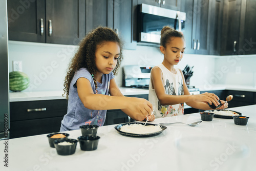 Girls making pizza in home kitchen