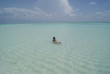 Girl swimming in a amazing beach of Maldives islands