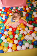 Fototapeta na wymiar Happy little kid girl play in the playing room pool full of colorful balls. Funny child having fun indoors. Birthday party