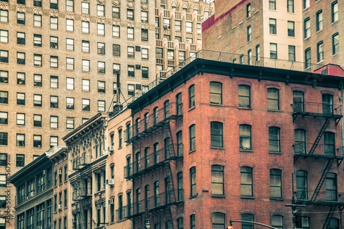 Photo  Vintage tenement buildings and modern buildings in the background, New York City