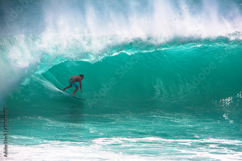 Surfer riding big wave at Padang Padang beach, Bali, Indonesia