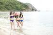 Group of beautiful young single chinese women having fun on beach. Walking on beach, wearing bikini, beach hat.