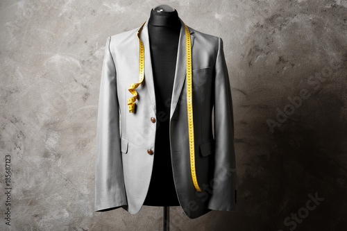 Photo Custom-made suit on mannequin against grey background
