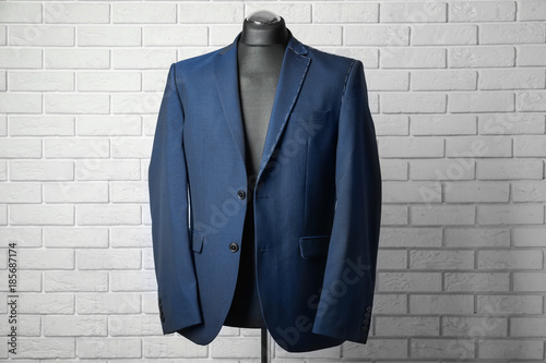 Fototapeta Semi-ready suit on mannequin against brick wall background obraz