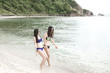 Group of beautiful young single chinese women having fun on beach. Walking on beach, wearing bikini, beach hat.