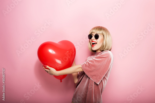 Photo  Beautiful young woman hugging in the shape of a heart red ball and smiling