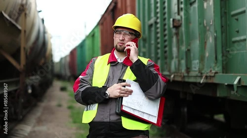Railway worker talks on mobile phone near goods trains. Railway employee stands between goods trains and speaks on cell phone, manager of works communicates via smartphone on freight station