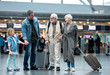 Unexpected meeting. Full length of cheerful aged couple with suitcases are standing at international airport with adult man and his little daughter. They are talking to each other with smile