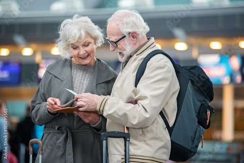 Obraz What time our plane. Involved gray-haired couple is standing at airport terminal and holding flight tickets. They are checking travel documents while discussing together with smile - fototapety do salonu