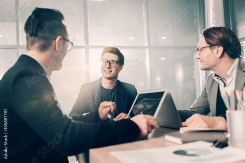 Fototapety, obrazy: Cheerful young partners telling with each other while locating at desk in office. Career concept