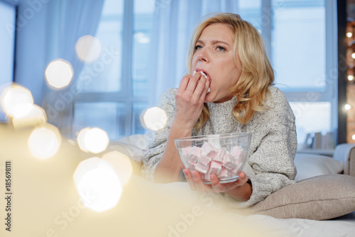 Portrait of upset female lying at home and filling mouth with marshmallow rapidly Canvas-taulu