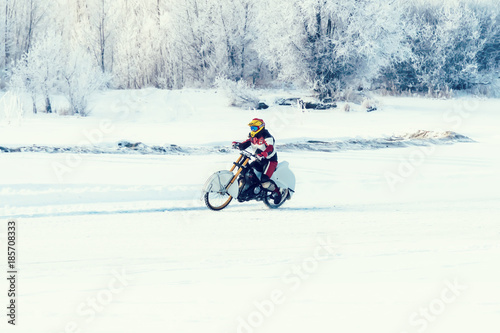 Fotografiet  Motorcycle traveler on snow winter steppe road path