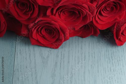 czerwone-roze-na-jasnoniebieskim-tle-drewna