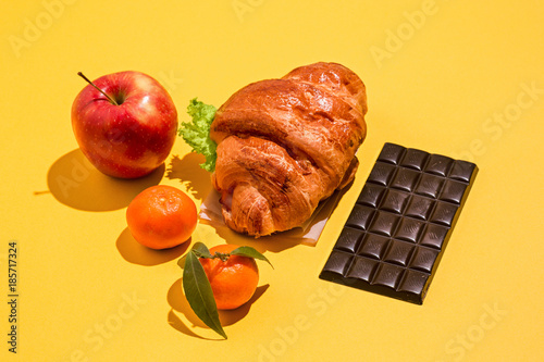 The apple, chocolate and croissants on yellow background Canvas Print