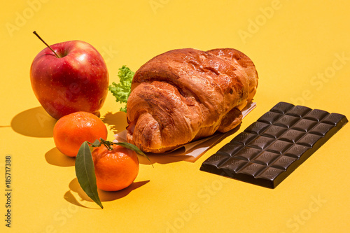 Fotografie, Tablou  The apple, chocolate and croissants on yellow background