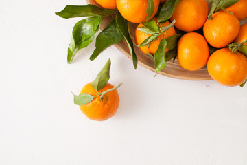 Fresh tangerines with green leaves on a white background