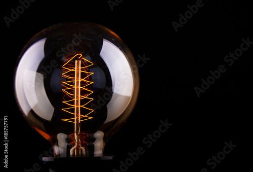 Cuadros en Lienzo classic Edison light bulb on black background