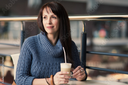 Fotografia  happy woman drinking coffee in cafe